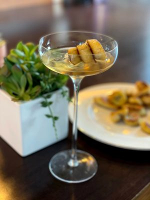 cocktail with a long stem in front of bananas and green plant