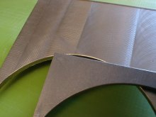 This photo vividly shows the difference between an as machined surface (the upper coupon with the fly-cutter milling) and the test coupon below which has had milling marks blended in, and a typical isotropic surface finish developed with centrifugal barrel finishing