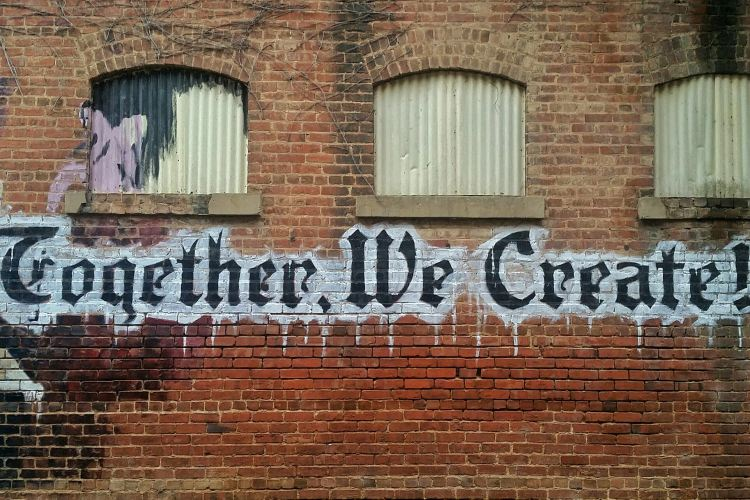 "Brick building with ""Together, We Create!"" spraypainted on it"