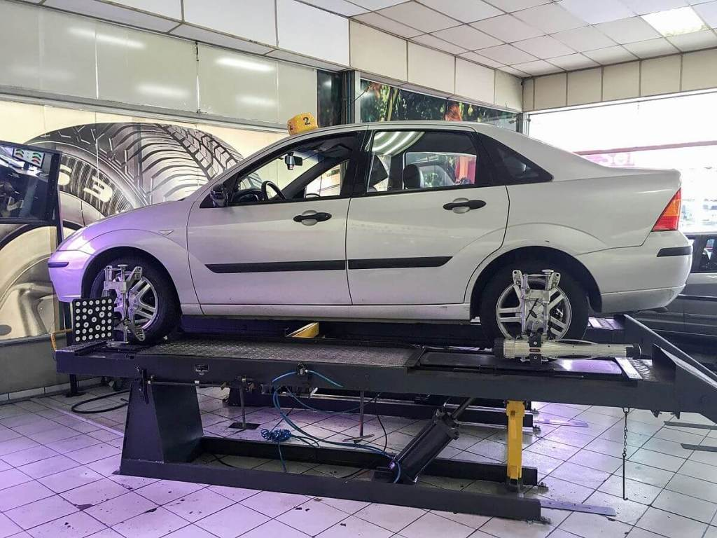 A car is sitting on top of an alignment machine, undergoing camber, caster and toe alignment.