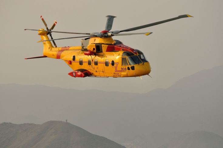 yellow helicopter flies above mountains in the haze