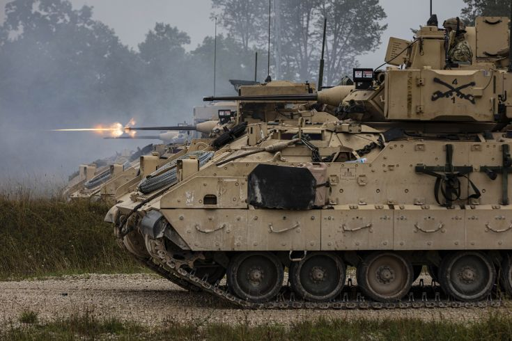 a row of tracked combat vehicles firing weapons
