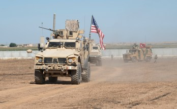 Military vehicles carrying flags in the desert