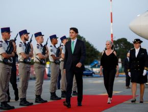 justin trudeau walks on a red carpet in front of a military guard