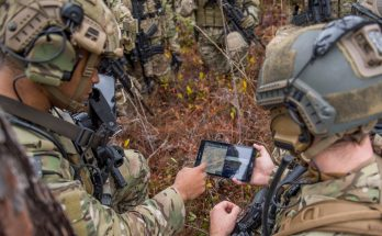 soldiers look at a tablet during training