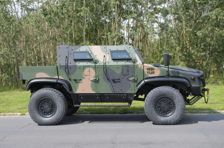 armored vehicle on the side of a road with greenery in the background