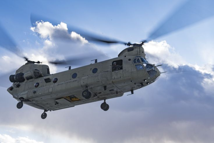 close-up of an Army helicopter in front of blue sky and clouds