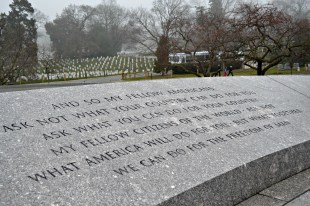 John F. Kennedy's inaugural address, engraved in the walls of his memorial, protect his final resting place and the Eternal Flame.