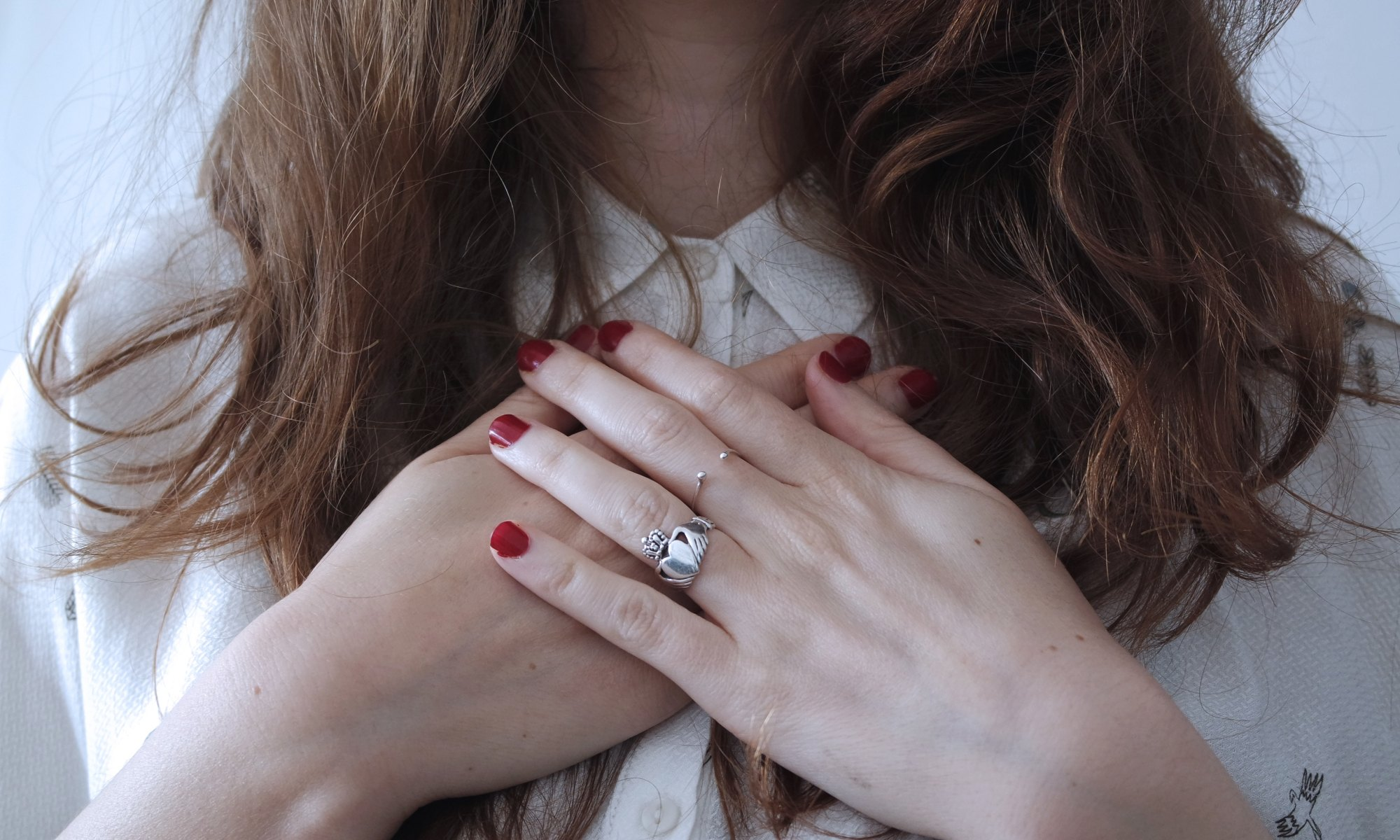 Brunette woman expressing self-love with her hands on her chest
