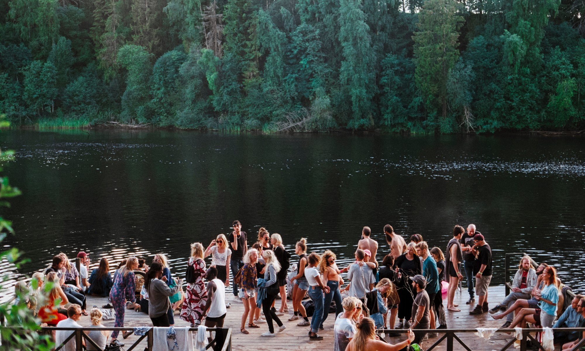 People socializing beside lake and forest