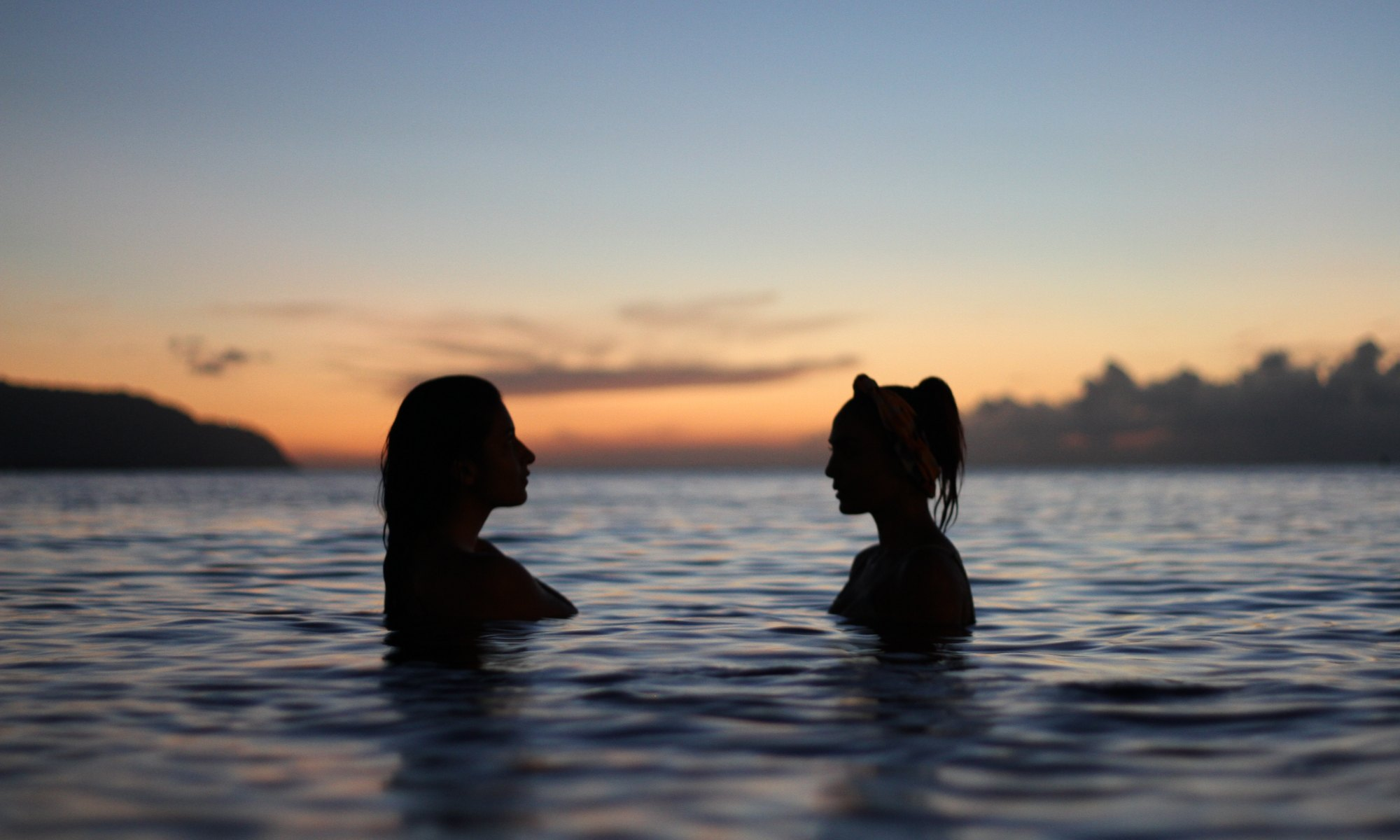 Silhouette of two women listening to each other in water