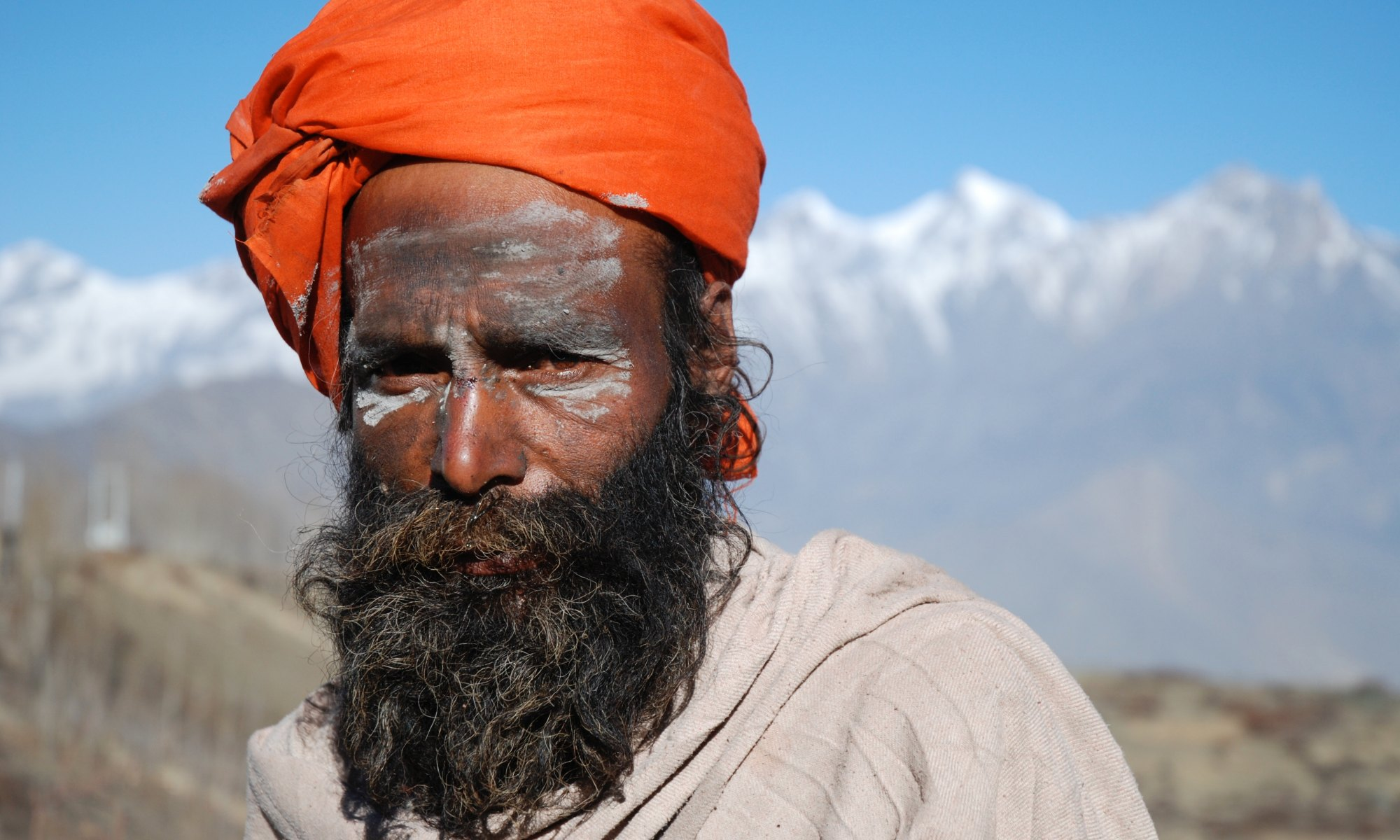 Brown man with big beard being authentic and wearing orange turban