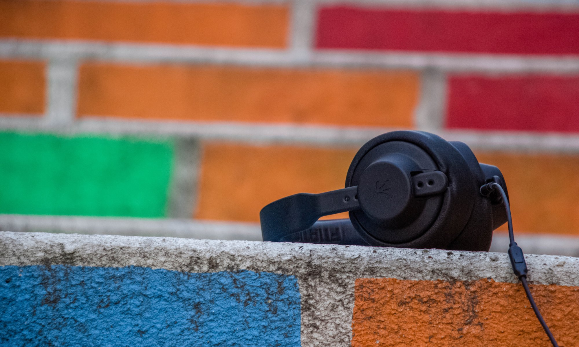 The healing effects of music from a black headphone around a colorful bricked wall