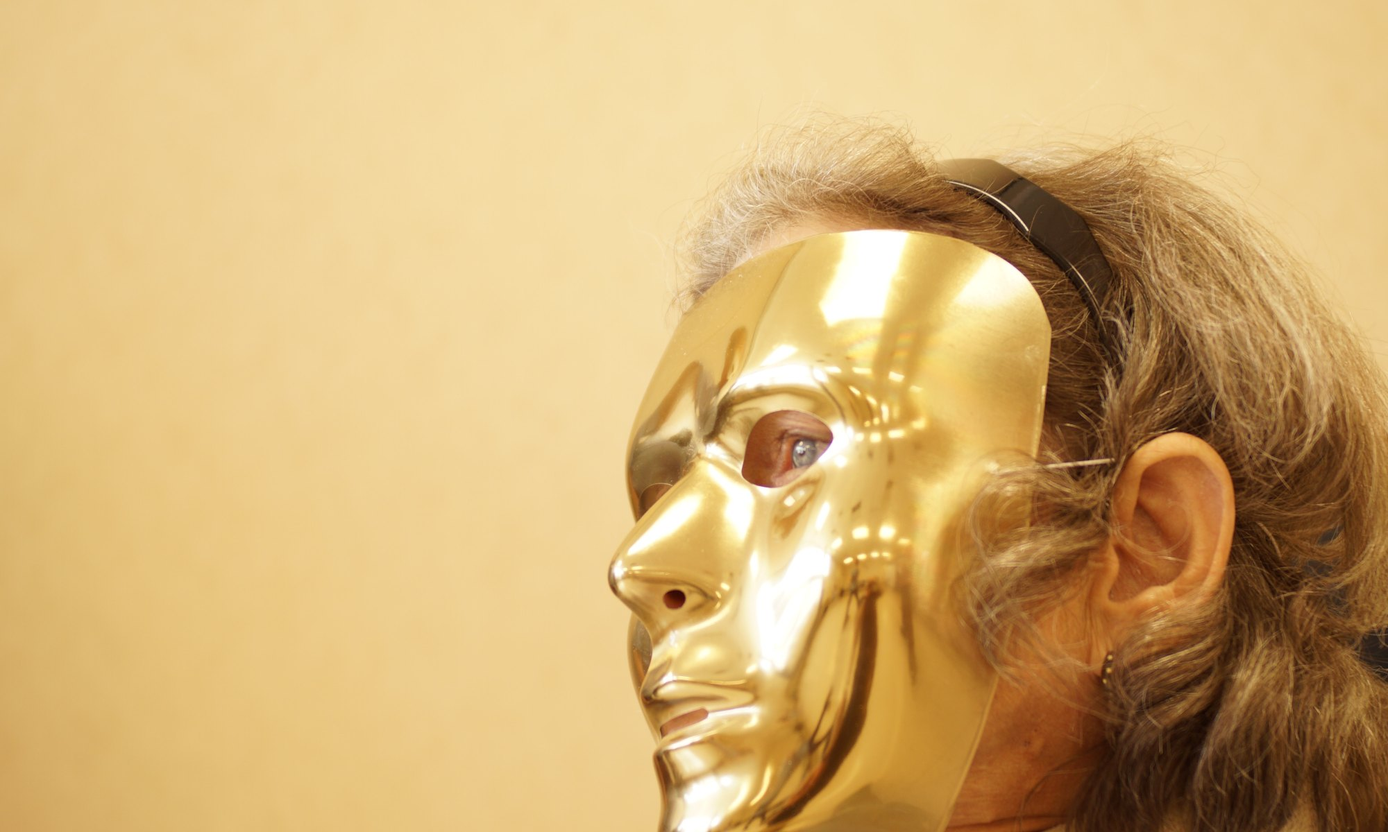 Person demonstrating theory of mind by wearing a gold mask