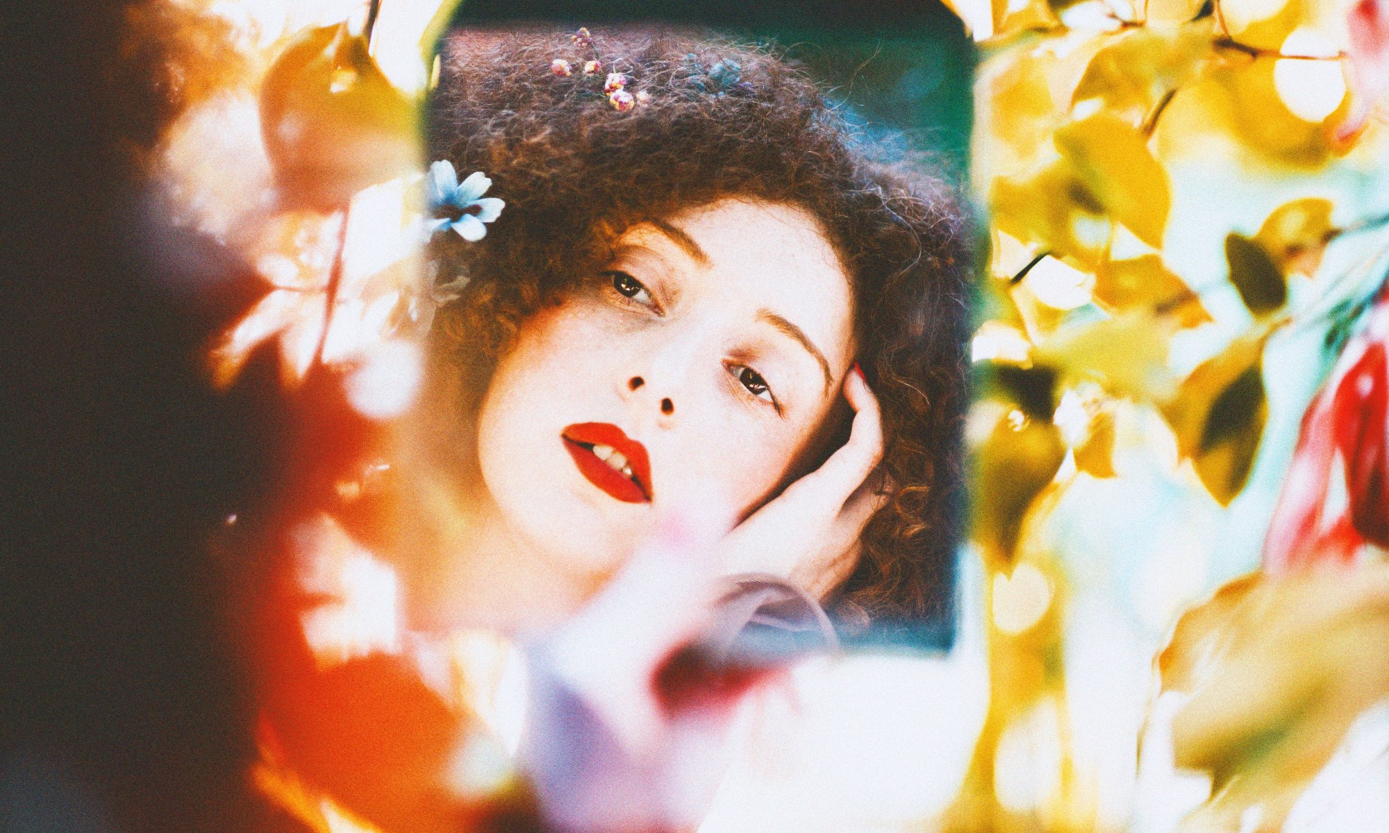 Brunette woman with red lipstick performing mirror meditation
