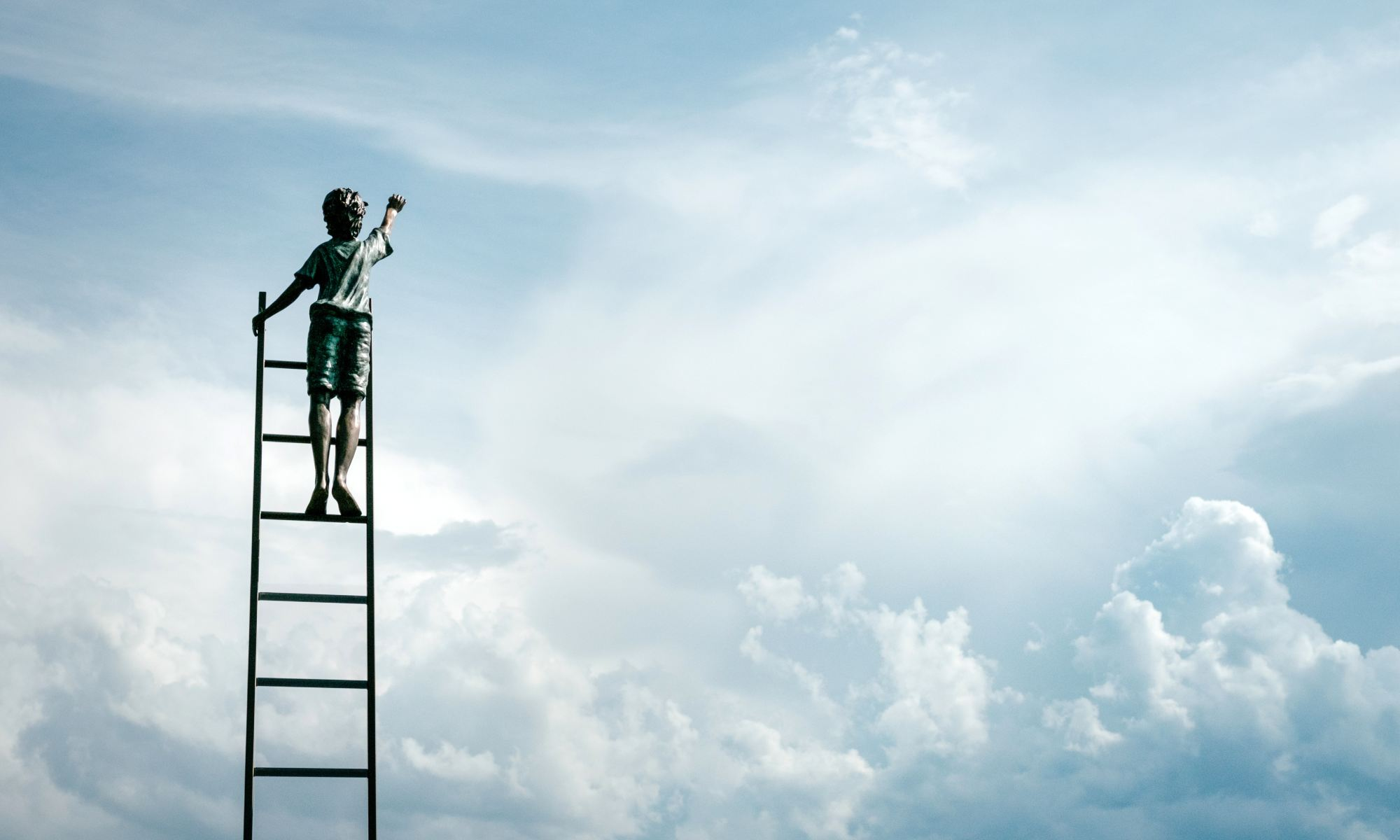 Inspired boy standing on ladder reaching for the clouds