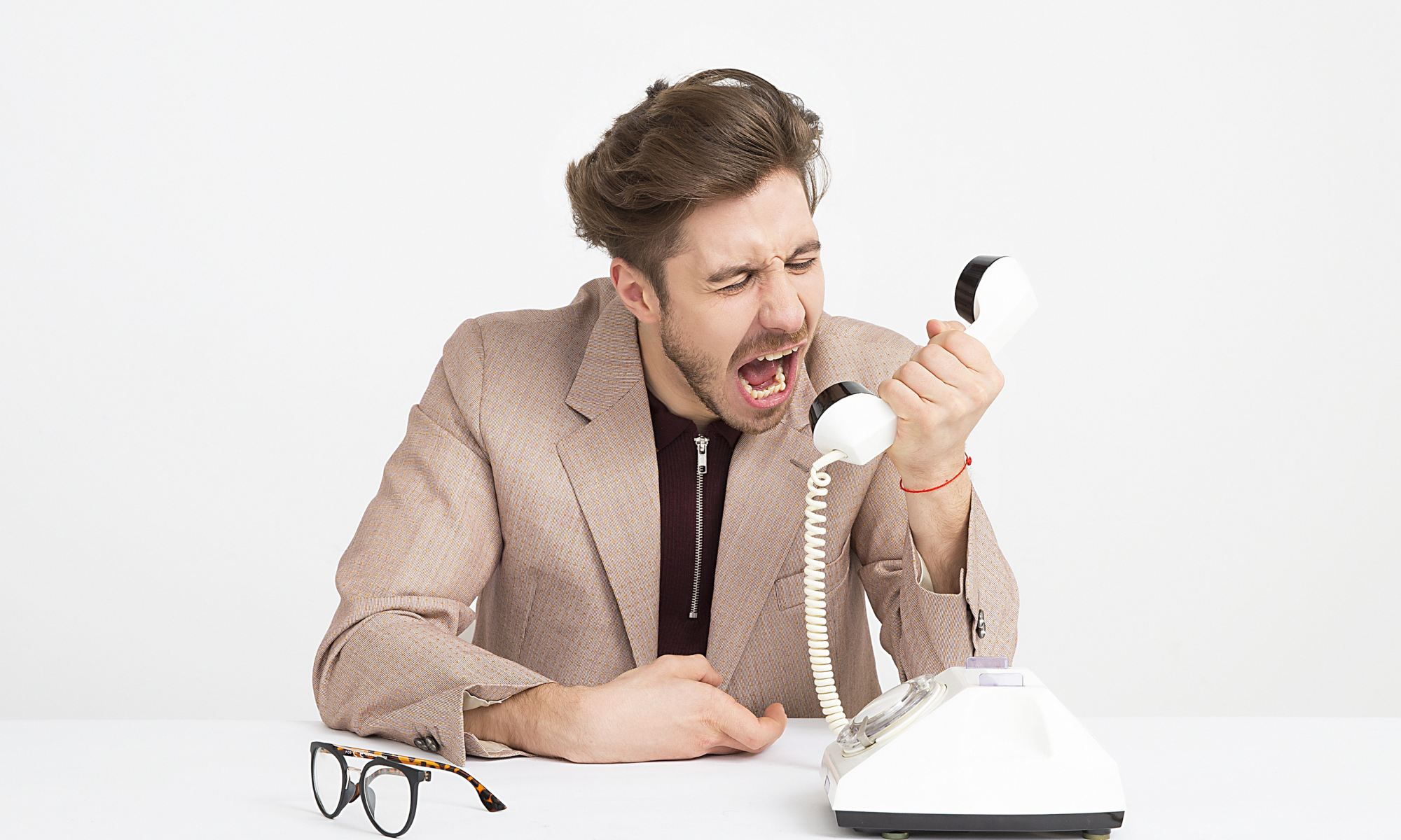 Man holding white telephone at work screaming and arguing