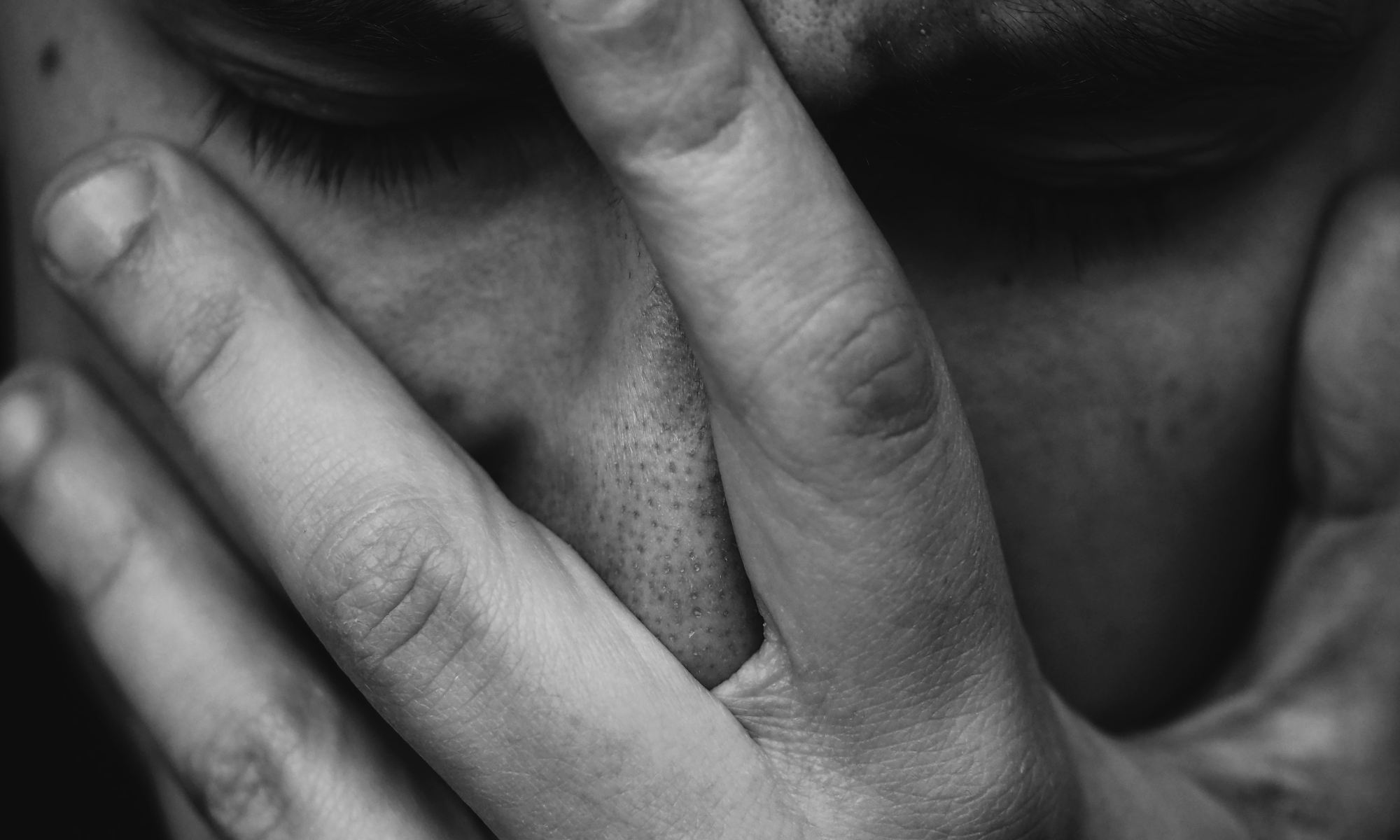 Grayscale photo of disappointed man holding hand on his face
