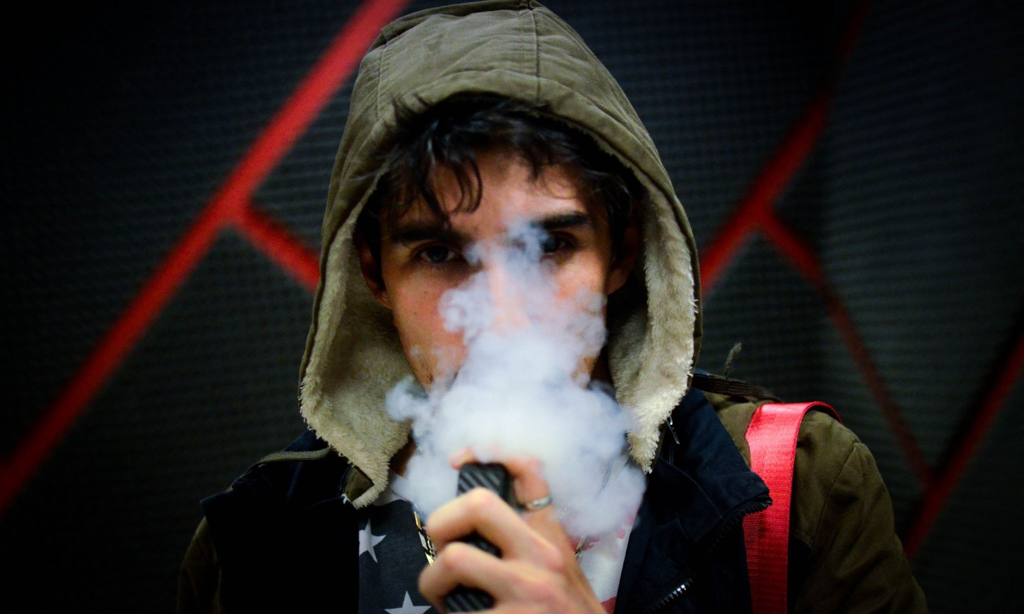 Young man in hoodie vaping a nicotine-containing product
