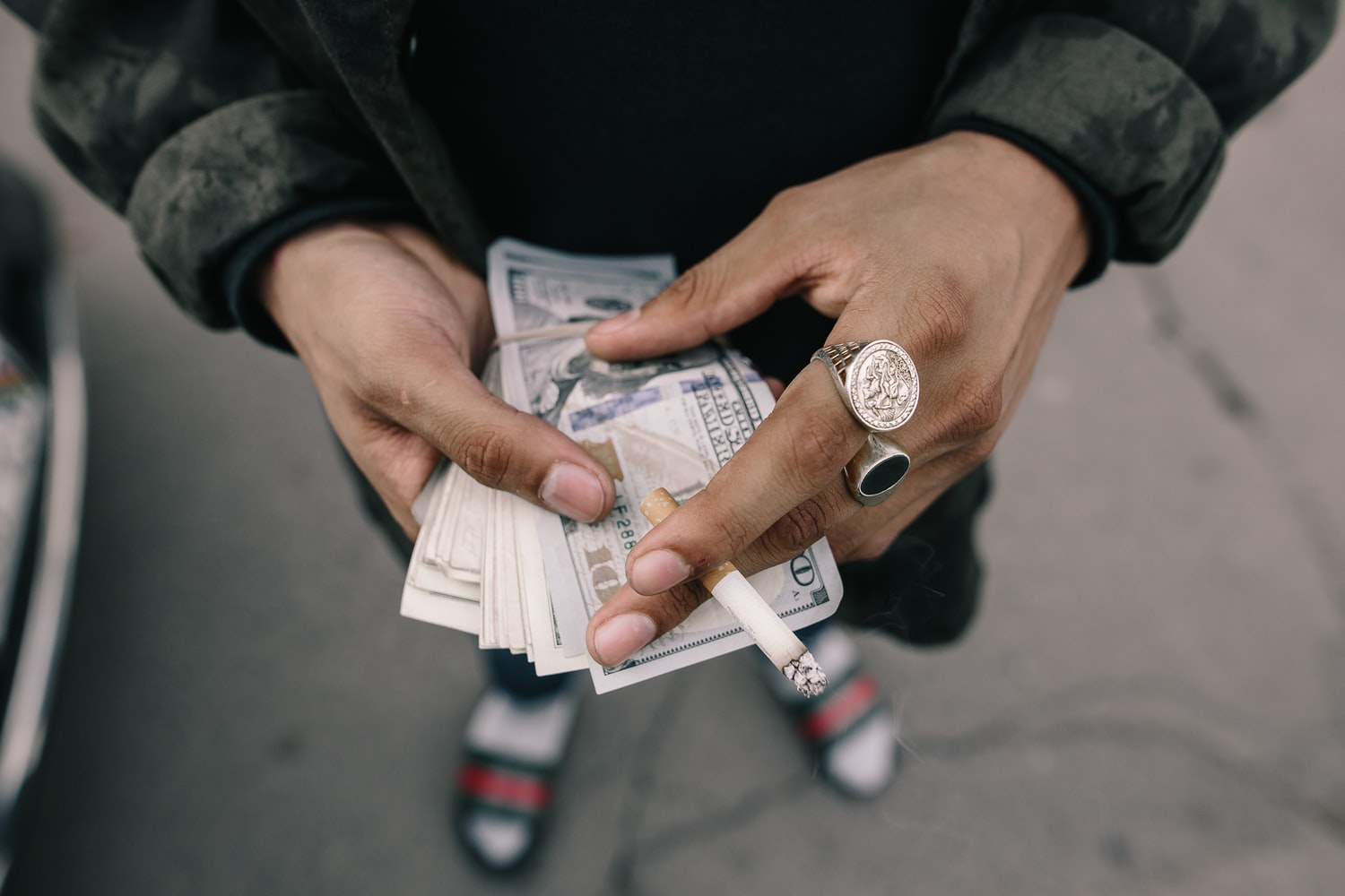 Drug addict holding cash and cigarette in hand