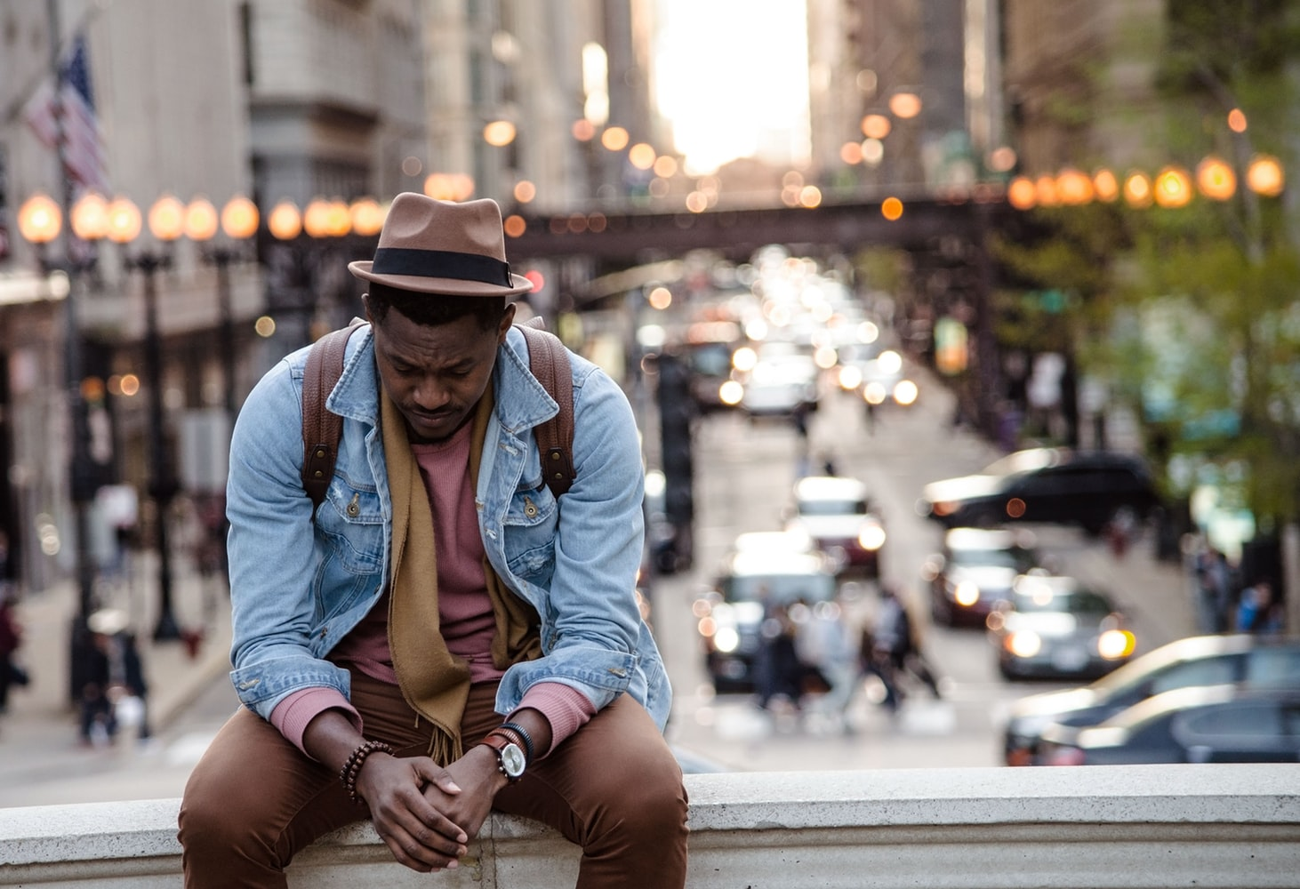 Sad African American man looking down while sitting on a ledge in a city