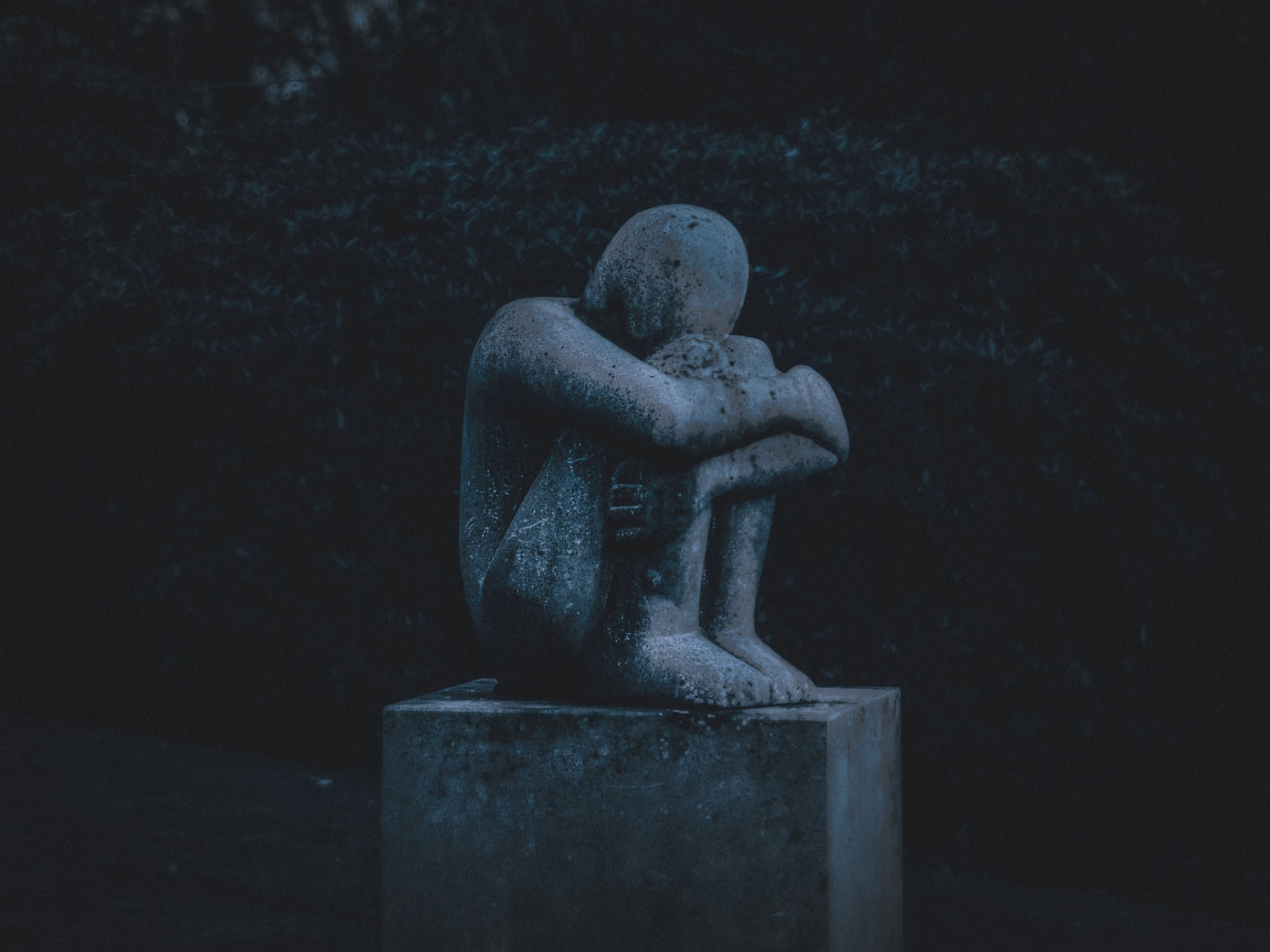 Statute of disappointed man hugging his knees