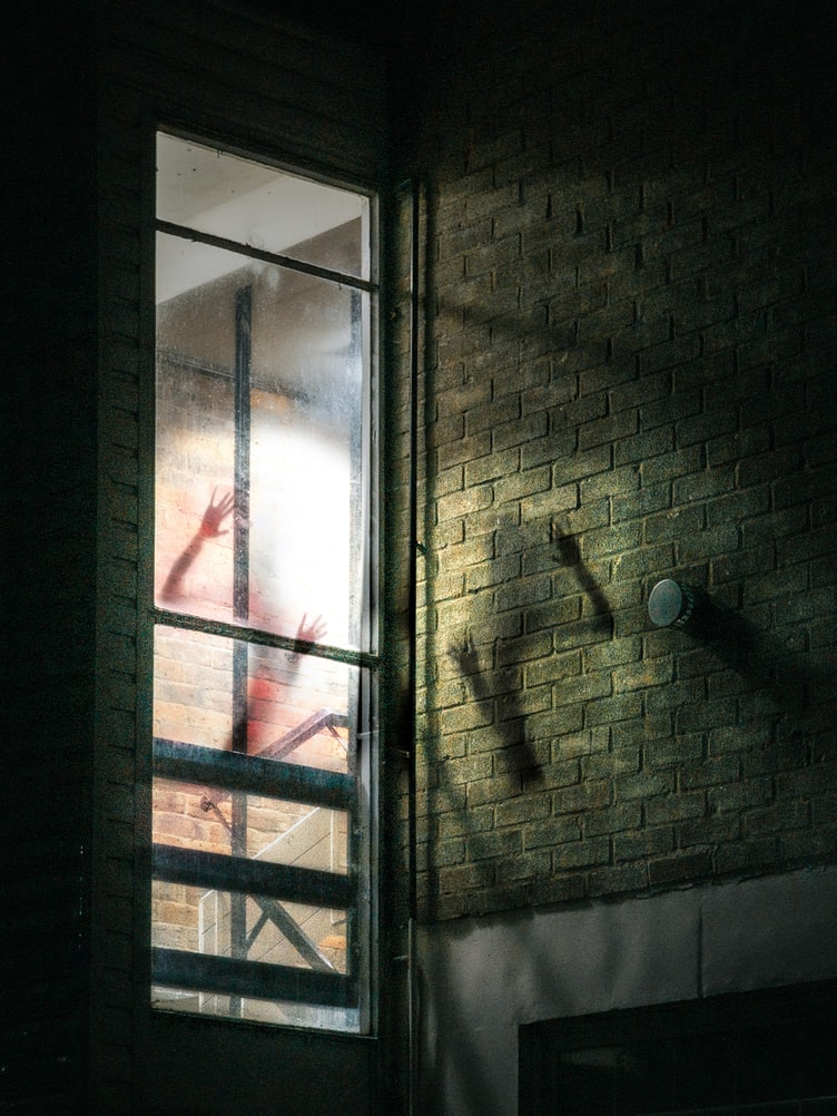 Evil person behind tall window of a brick building