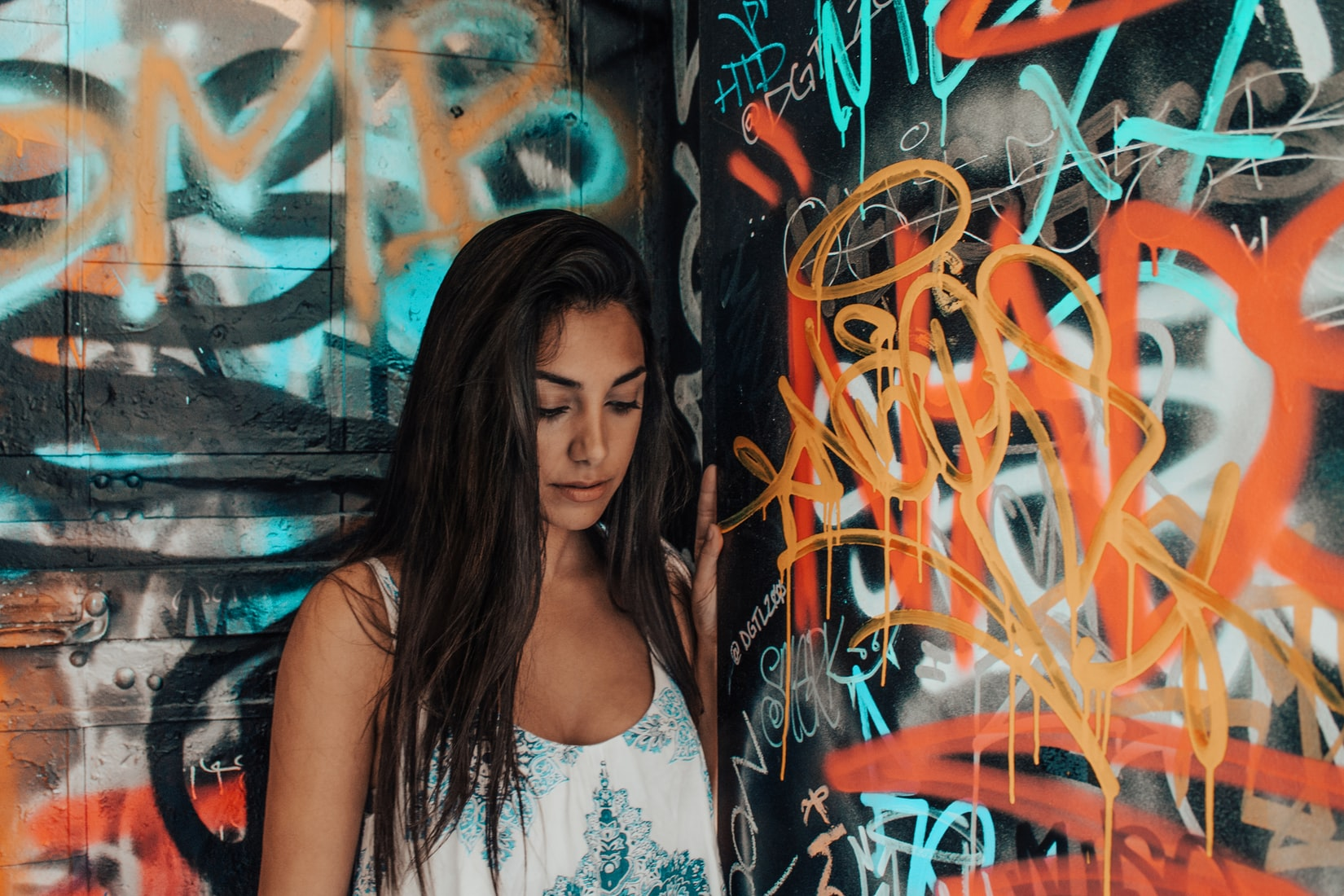 Young brunette woman experiencing negative thoughts while standing next to graffiti wall