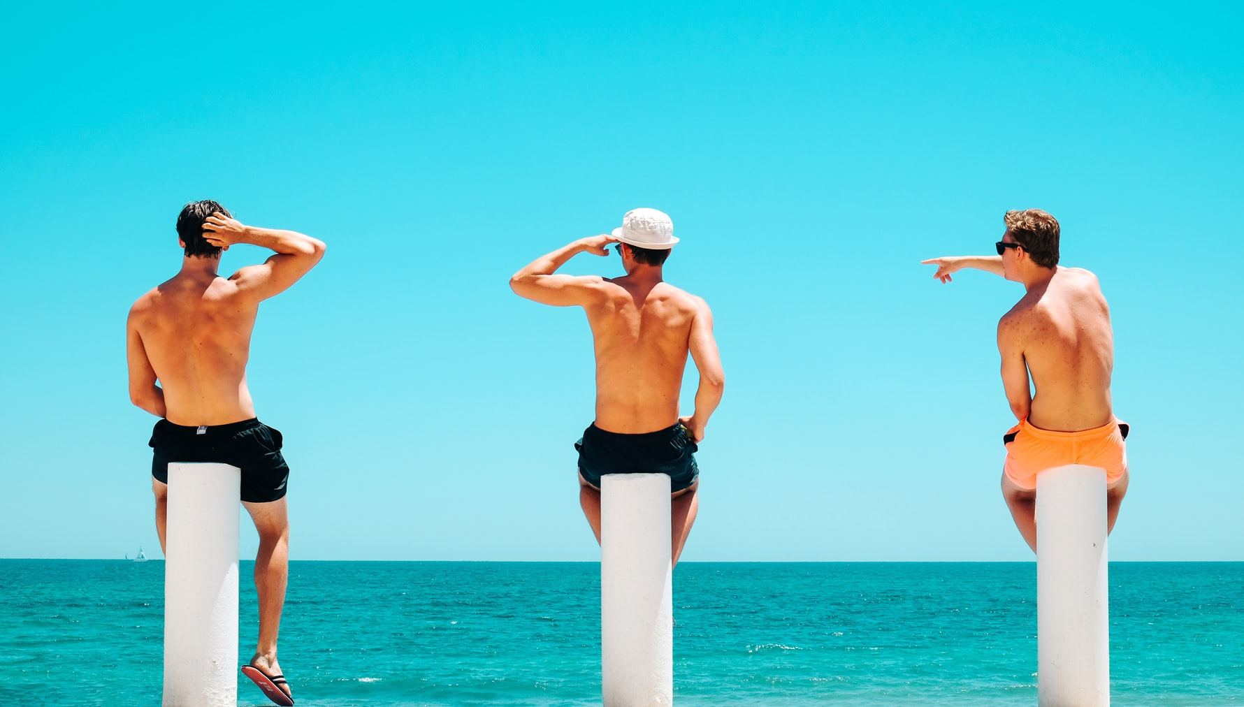 Three white men sitting on white concrete bollards in front of tropical water