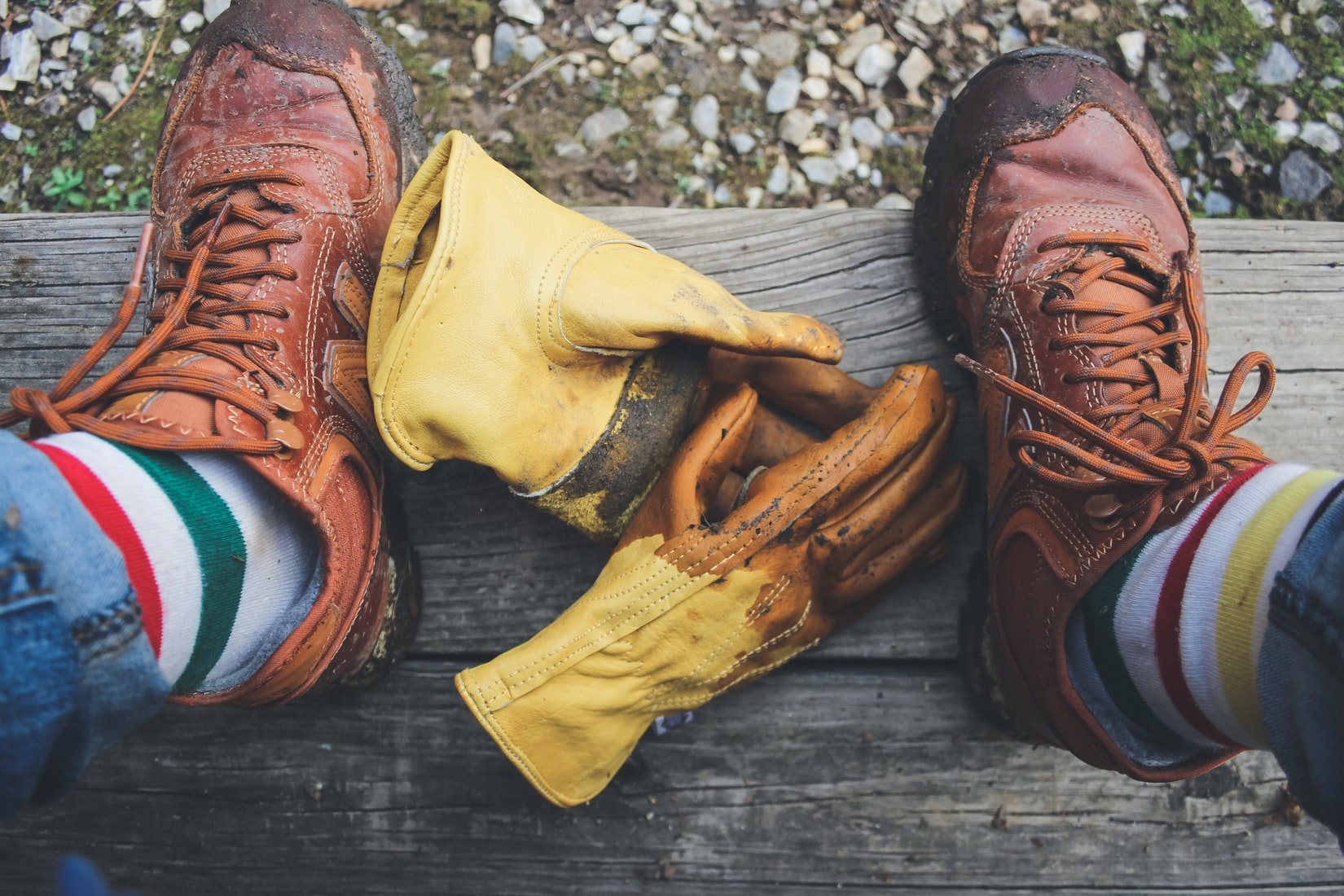 Pair of yellow gloves on ground in-between man's brown shoes
