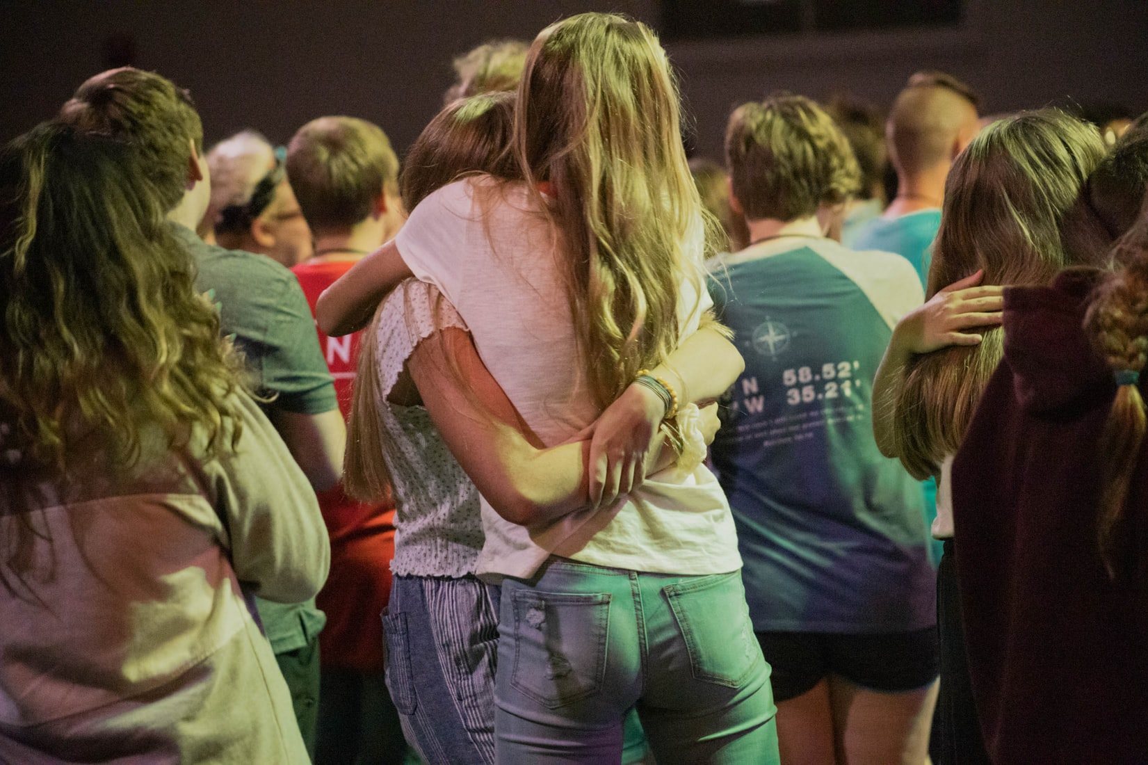 Group of young people hugging each other