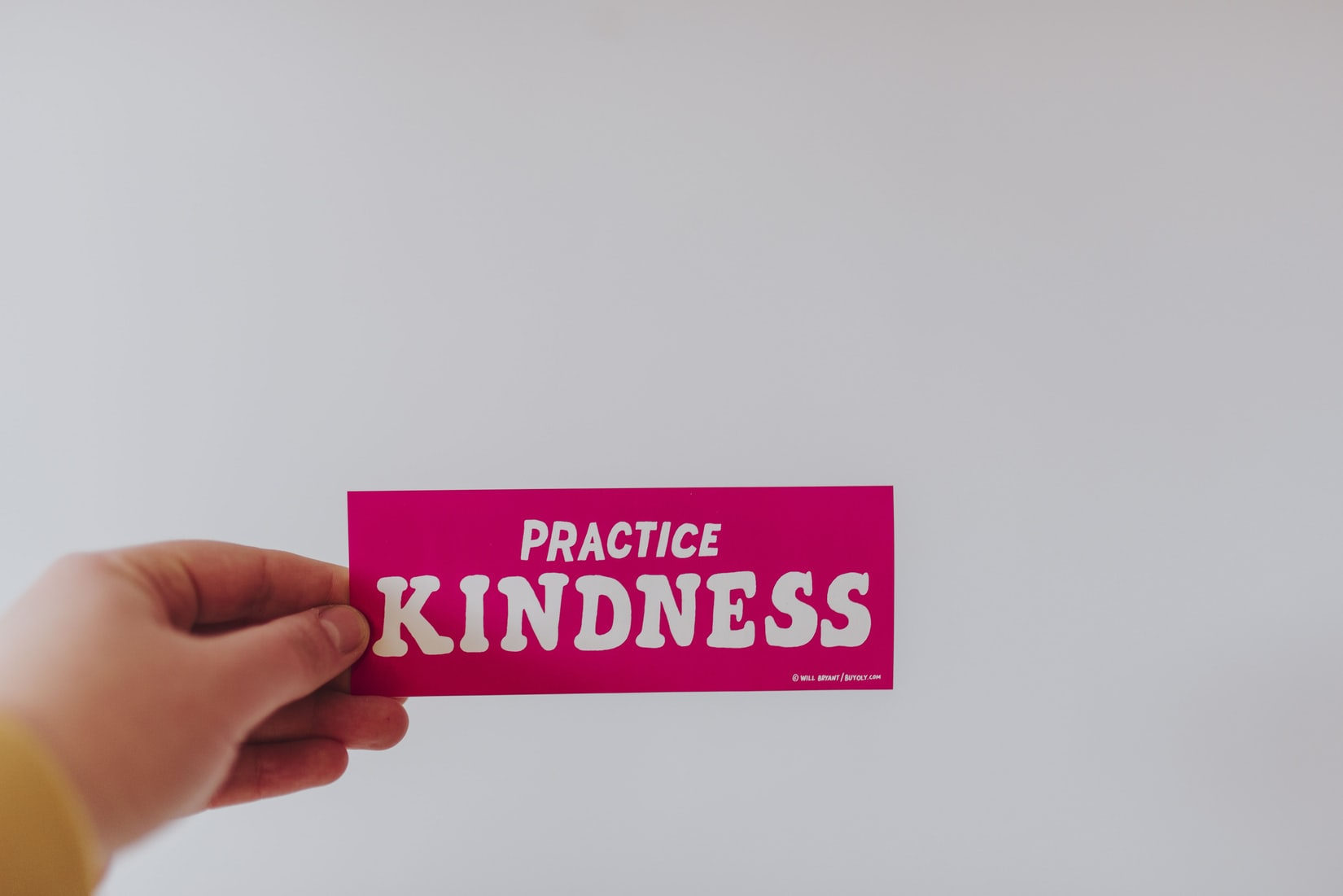"""Hand holding red and white """"practice kindness"""" sticker"""