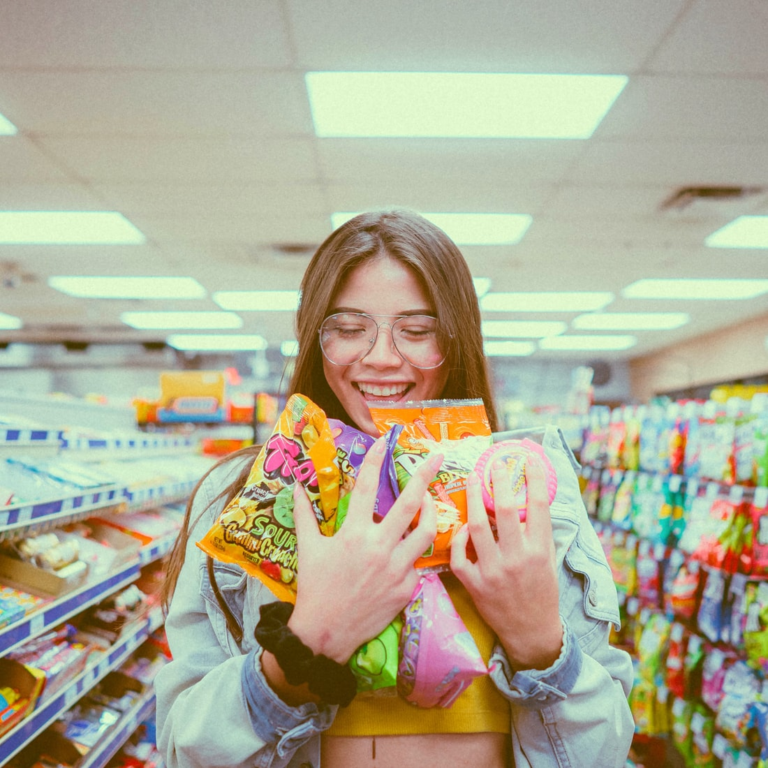 Young brunette woman smiling while holding pack of candies inside grocery store