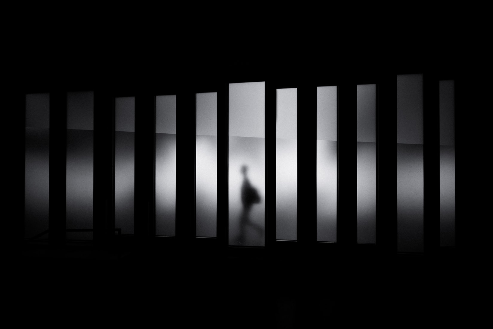 Grayscale photo of person with backpack walking in black and gray panel paintings