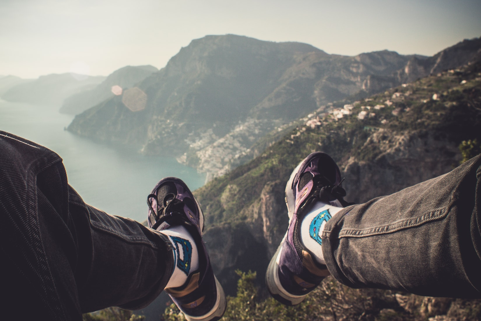 Happy person sitting on cliff over body of water during daytime