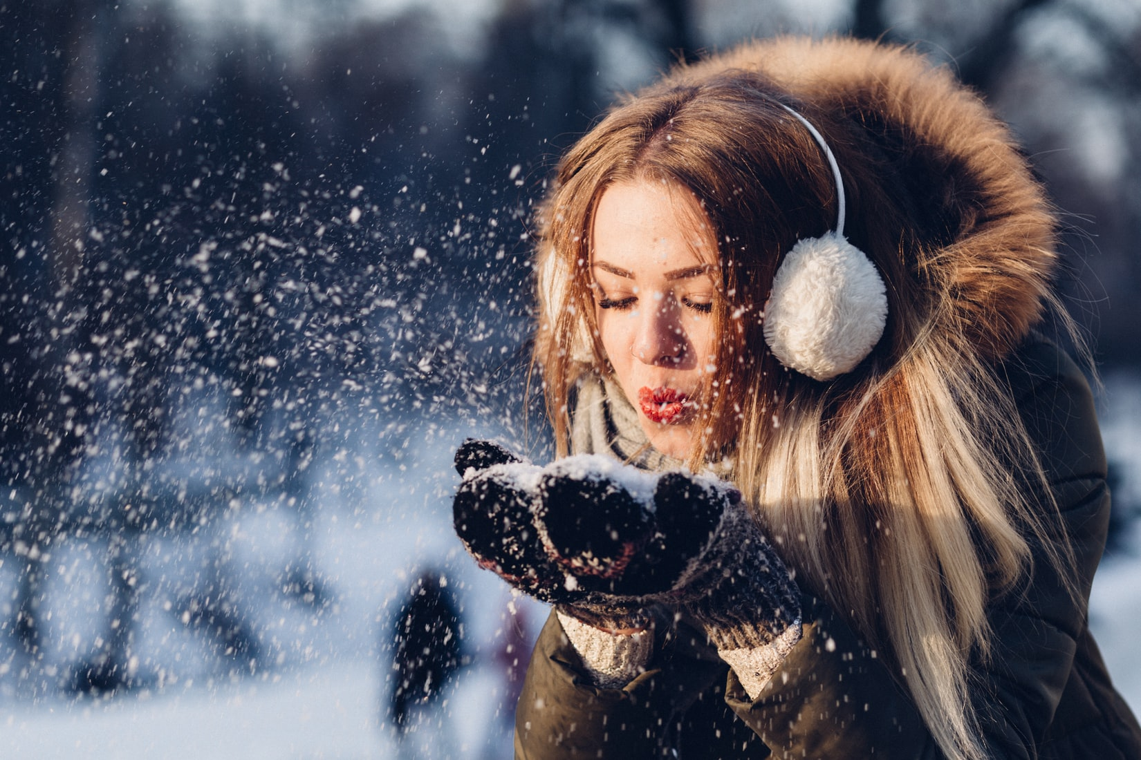 Young brunette woman wearing winter coat and blowing snow on her gloves outdoors