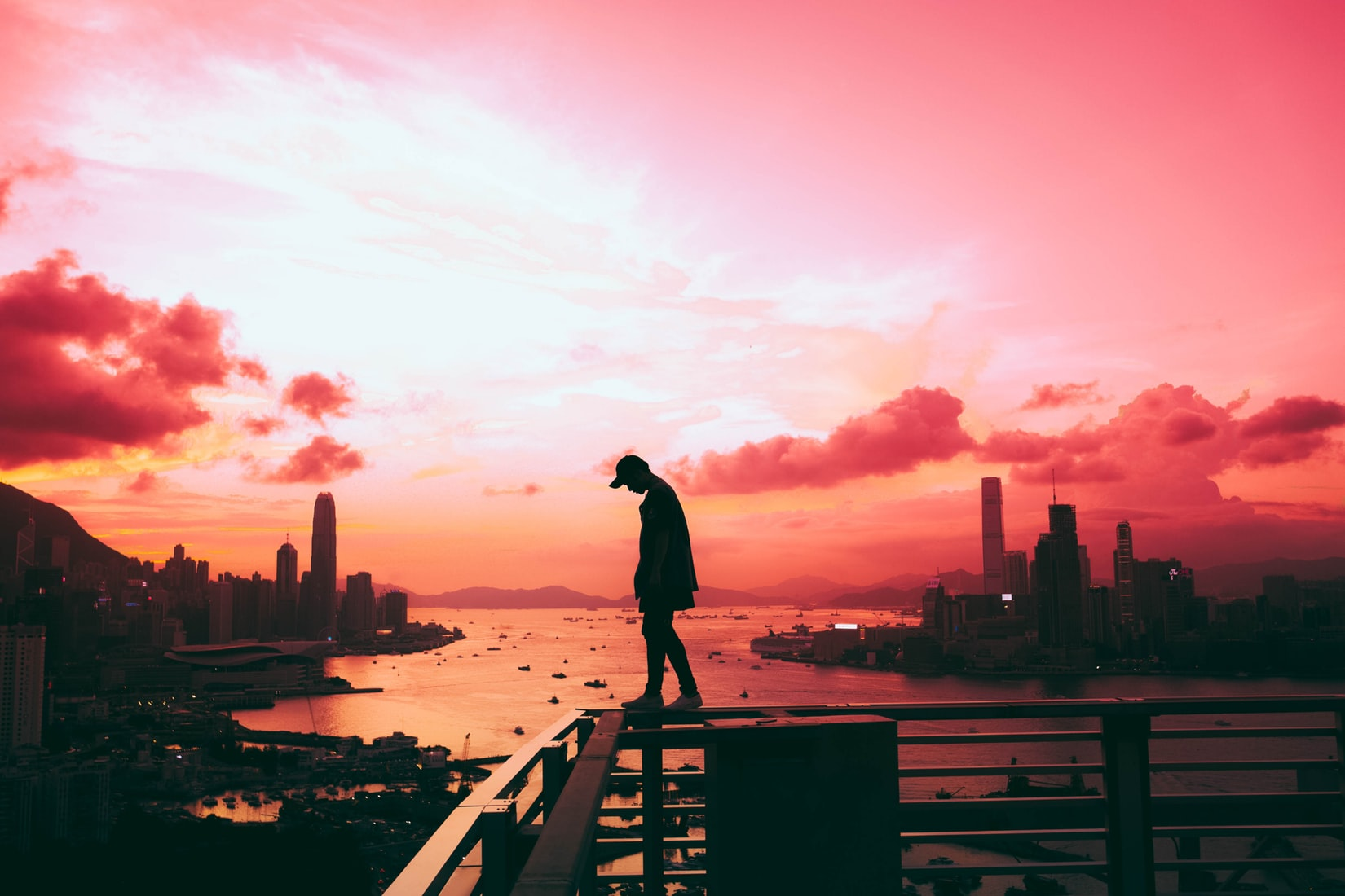 Silhouette of lonely man standing on railing of building in front of body of water and city