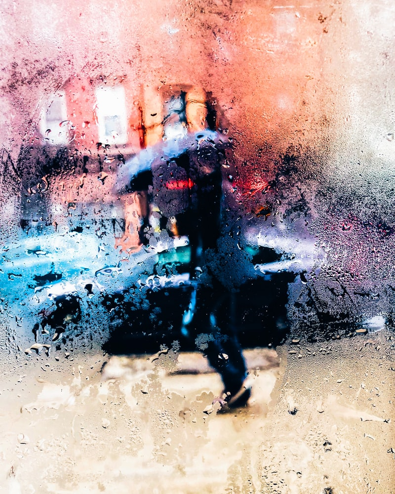 Person holding umbrella while walking in the rain on sidewalk