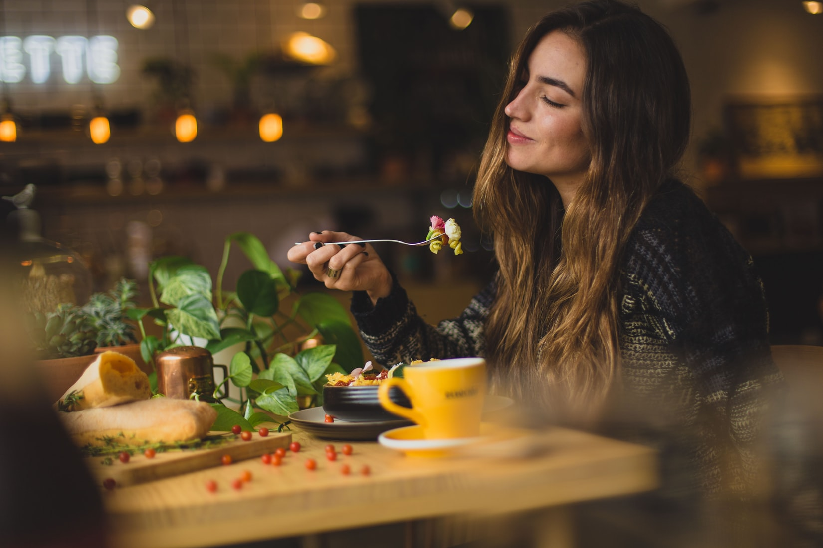 Young brunette woman smiling while eating pasta at wooden table