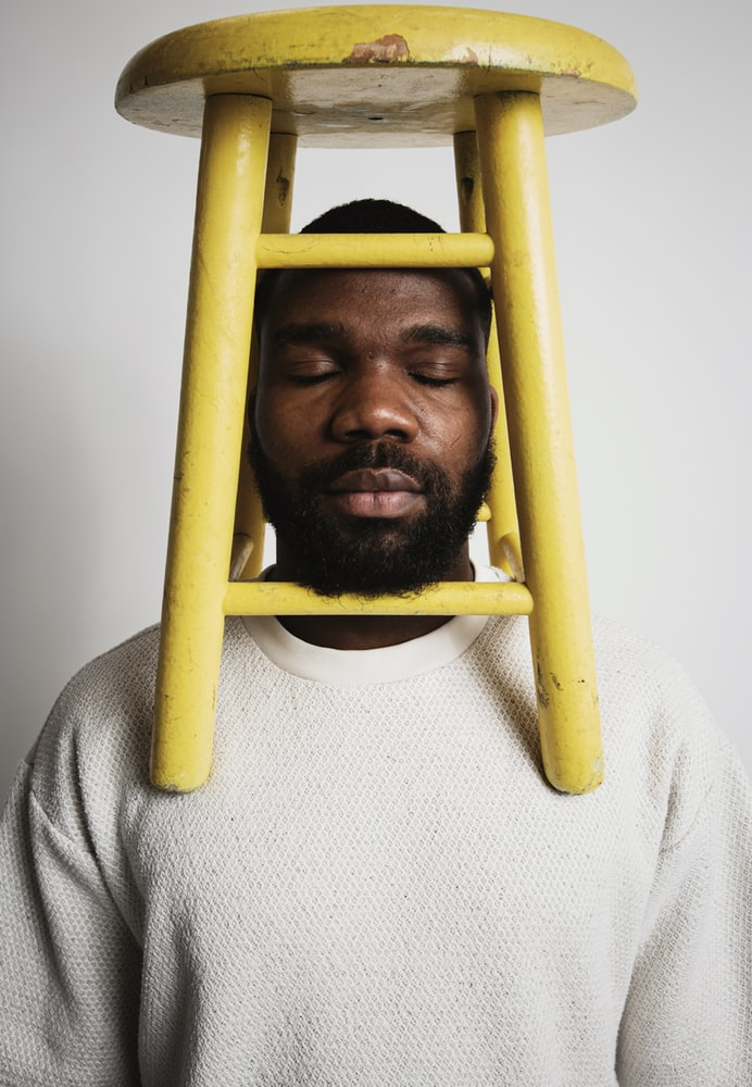 Black man with yellow wooden stool on top of shoulders and head