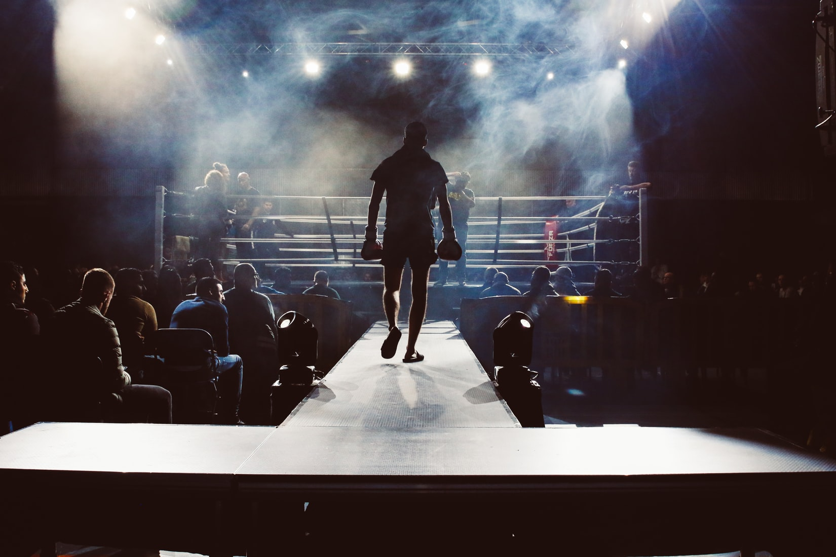 Man walking towards boxing ring surrounded by audience
