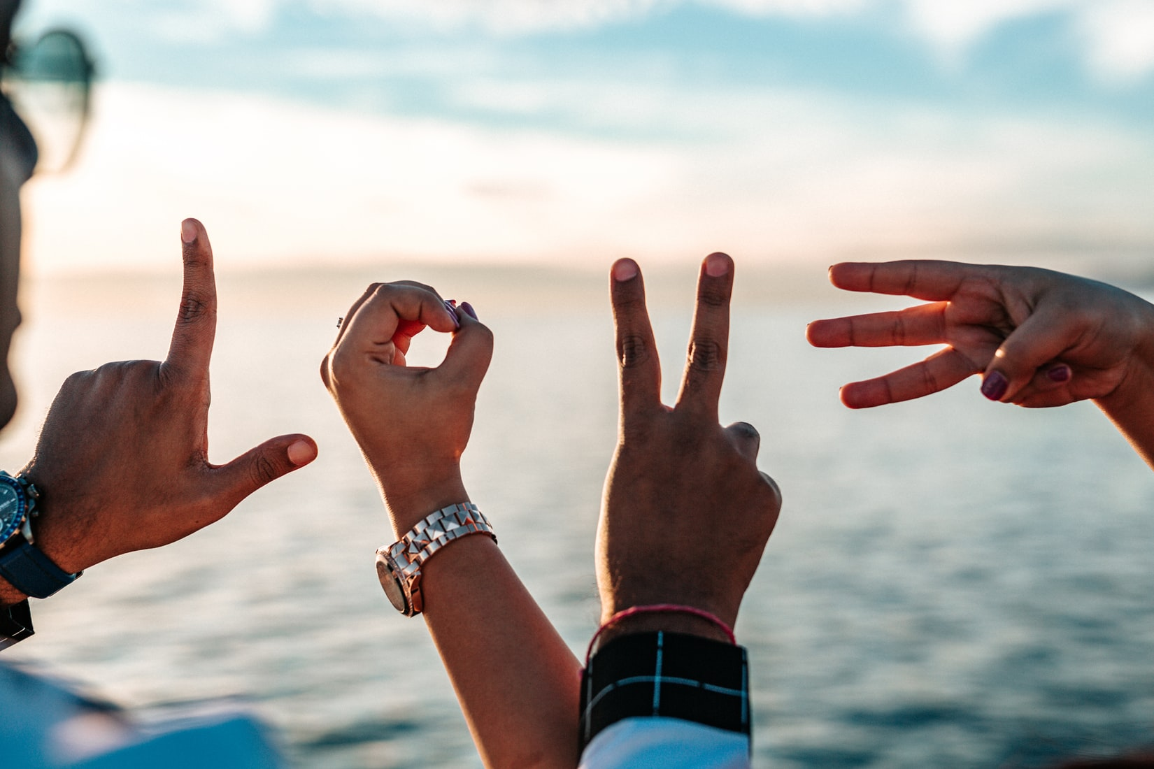 Two persons forming love fingers in front of body of water