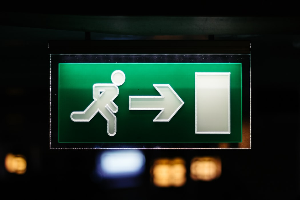 Closeup photo of green and white signage of person running towards arrow and door