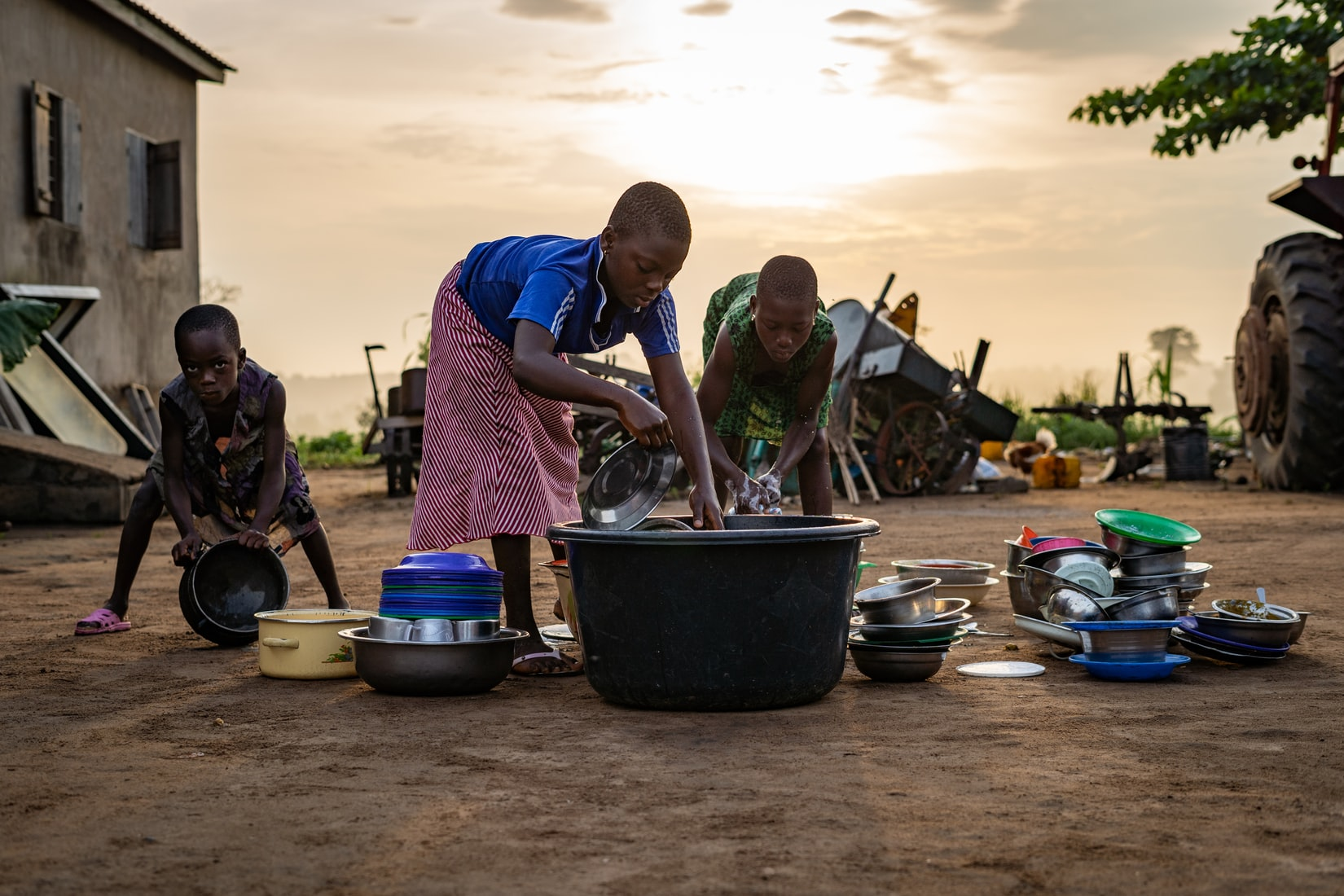 Black African children washing dishes outside
