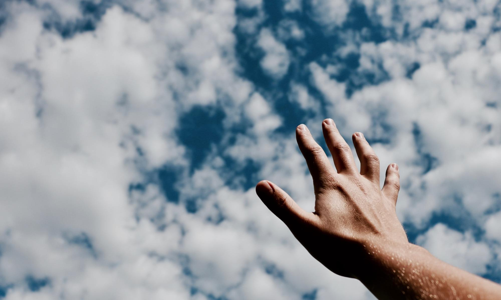 Person's hand reaching for the cloudy sky