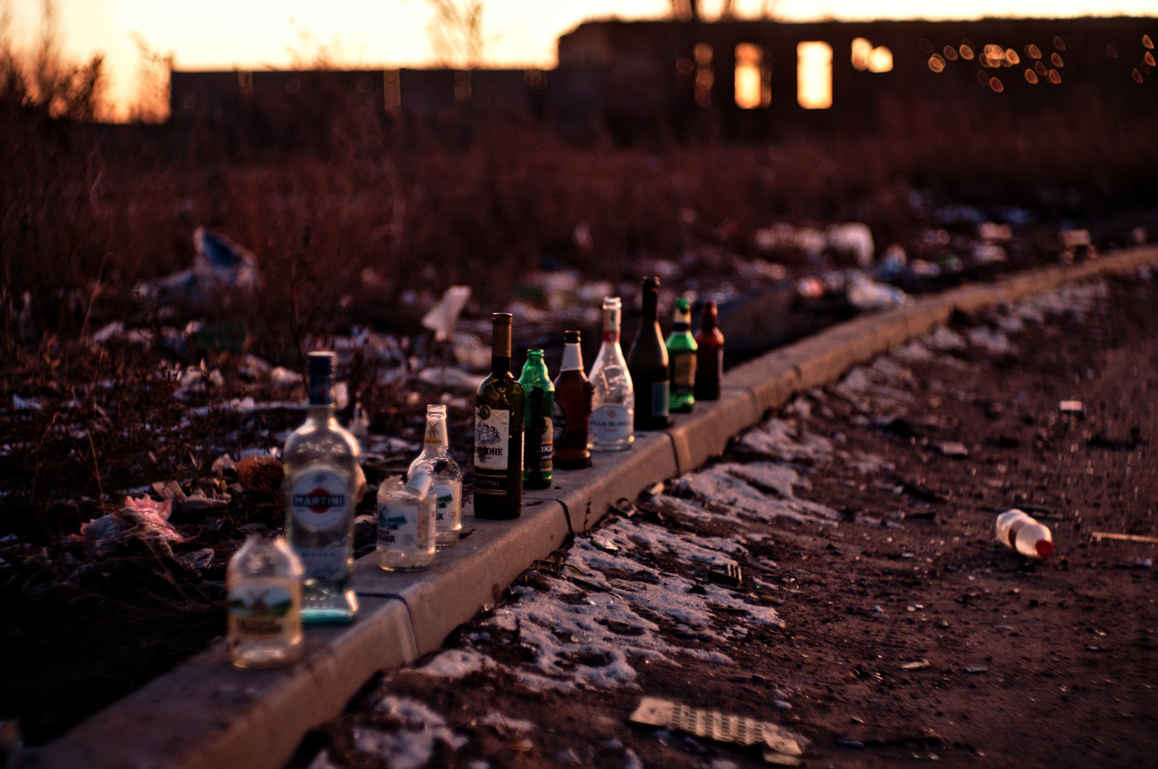 Bottles of liquor lined up on concrete surface outside