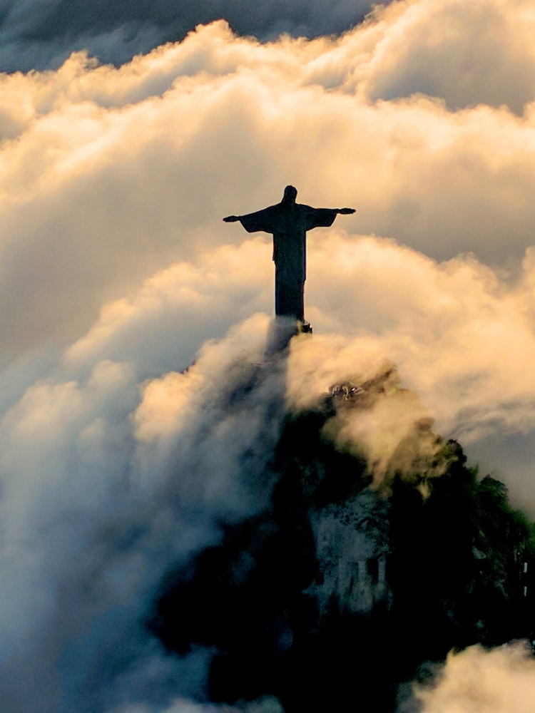 Jesus Christ statue on mountain surrounded by clouds