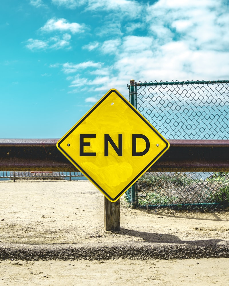 Yellow end sign on sand in front of fence