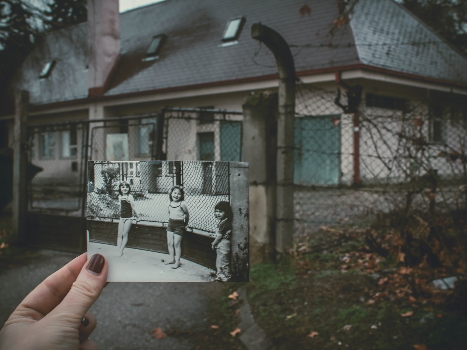 Person holding gray photo of three girls near chainlink fence around house