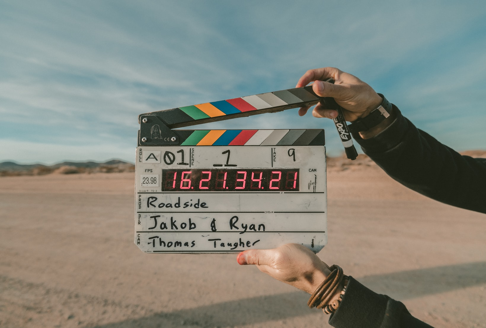 Person holding clapperboard in front of desert